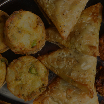 A photograph showing a selection of samosa's and other Indian platter food