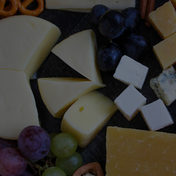 A photograph showing a selection of cheeses and grapes