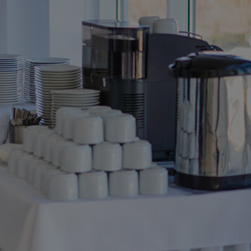 A photograph showing tea and coffee thermos' alongside a pile of mugs and cups