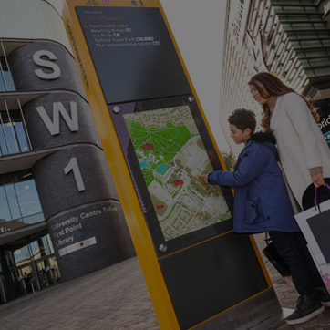 A photograph showing a mother and child using a wayfinder totem in Southwater