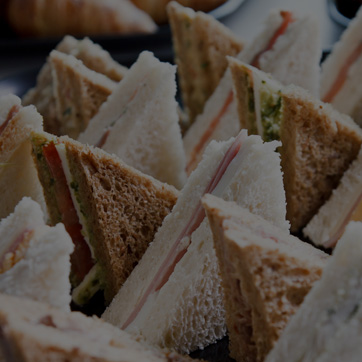 A photograph showing triangular sandwiches presented on a platter