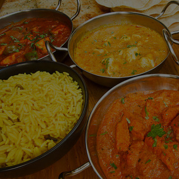 A photograph showing a selection of Indian curries in various shaped bowls