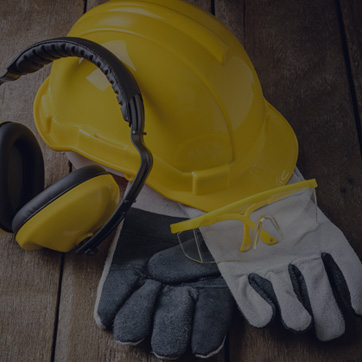 A photograph of a hard hat, protective gloves and ear defenders