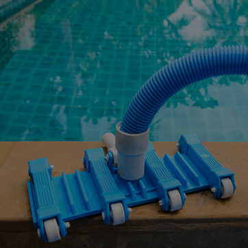 A photograph of an automated pool cleaner by the side of a swimming pool