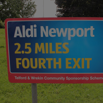A photograph of a roundabout sign