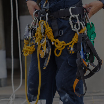 A photograph of a person wearing a harness with ropes